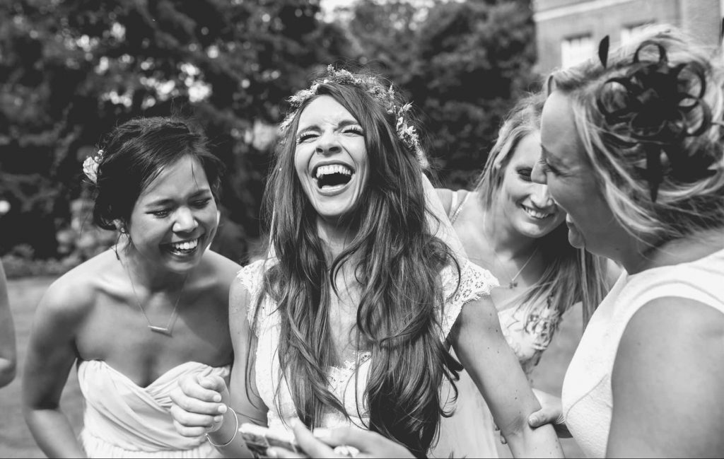 Wedding Photographer in Cambridge catching a moment of a bride laughing with her bridesmaids